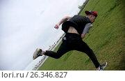 Купить «Acrobatic movement with rotation in slow motion. Teenager male performing acrobatic jump in park, camera turns together with the athlete», видеоролик № 26346827, снято 20 апреля 2018 г. (c) Константин Шишкин / Фотобанк Лори