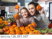Купить «Blonde girl with mother buying mandarins in shop», фото № 26351107, снято 21 марта 2016 г. (c) Татьяна Яцевич / Фотобанк Лори