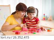 Купить «Child and therapist playing with toy the sand. Psychologist works, sand therapy.», фото № 26352415, снято 17 марта 2017 г. (c) Оксана Кузьмина / Фотобанк Лори