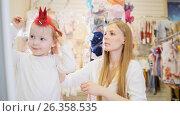Купить «The girl tries red rim in mall - clothes store», фото № 26358535, снято 20 апреля 2018 г. (c) Константин Шишкин / Фотобанк Лори