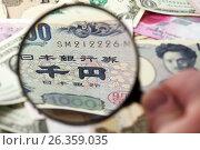 Купить «Лупа в руке фокусируется на японской йене в окружении различных валют», фото № 26359035, снято 9 июля 2009 г. (c) Александр Гаценко / Фотобанк Лори