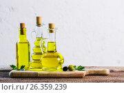 Купить «Olive oil on the wooden table», фото № 26359239, снято 23 мая 2017 г. (c) Майя Крученкова / Фотобанк Лори