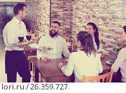 Купить «Waiter bringing order to visitors», фото № 26359727, снято 17 января 2017 г. (c) Яков Филимонов / Фотобанк Лори
