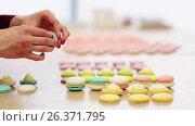 Купить «chef sandwiching macarons shells with cream», видеоролик № 26371795, снято 23 июля 2019 г. (c) Syda Productions / Фотобанк Лори
