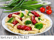 Купить «Delicious Spiral Pasta salad with broccoli and grilled sausages decorated with dill on a white dish with tomato sauce in a gravy boat, studio lights, close-up», фото № 26376827, снято 16 июля 2018 г. (c) Oksana Zh / Фотобанк Лори