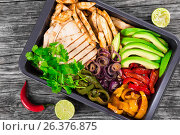 Купить «Delicious Chicken Fajita Platter with Avocado, Lime, Pita bread, Bell Pepper, Red Onion and Cilantro, close up, top view», фото № 26376875, снято 7 декабря 2019 г. (c) Oksana Zh / Фотобанк Лори