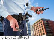 Купить «Composite image of mid section of security officer holding hand cuff and walkie talkie», фото № 26380903, снято 20 июля 2018 г. (c) Wavebreak Media / Фотобанк Лори
