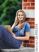 Купить «Молодая веселая девушка сидит на ступеньках с планшетом и смотрит на камеру», фото № 26410019, снято 13 июня 2014 г. (c) Александр Гаценко / Фотобанк Лори