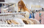 Купить «The girl chooses an outfit among a variety of women's clothes», фото № 26418551, снято 22 июля 2018 г. (c) Константин Шишкин / Фотобанк Лори