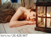 Romantic woman lying on a floor near retro lantern with candles. Стоковое фото, фотограф Дарья Зуйкова / Фотобанк Лори