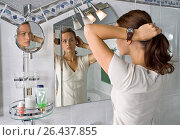 Купить «Young woman in bathroom dressing her hair», фото № 26437855, снято 18 сентября 2007 г. (c) age Fotostock / Фотобанк Лори