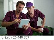 Baseball players using digital tablet while sitting on bench. Стоковое фото, агентство Wavebreak Media / Фотобанк Лори