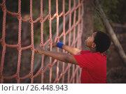 Купить «Determined boy climbing a net during obstacle course», фото № 26448943, снято 16 марта 2017 г. (c) Wavebreak Media / Фотобанк Лори