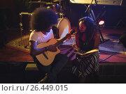 Купить «Performers practicing on stage in illuminated nightclub», фото № 26449015, снято 7 марта 2017 г. (c) Wavebreak Media / Фотобанк Лори