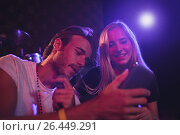 Купить «Young male and female musicians using mobile phone in nightclub», фото № 26449291, снято 7 марта 2017 г. (c) Wavebreak Media / Фотобанк Лори