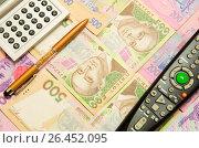 Купить «Калькулятор,ручка и пульт дистанционного управления лежат на купюрах украинских гривен», фото № 26452095, снято 21 августа 2019 г. (c) Игорь Кутателадзе / Фотобанк Лори
