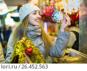 Купить «Young woman at fair near counter with Christmas gifts», фото № 26452563, снято 17 ноября 2018 г. (c) Яков Филимонов / Фотобанк Лори
