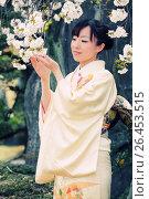 Купить «Японская девушка в светлом кимоно держит ветку сакуры», фото № 26453515, снято 27 марта 2011 г. (c) Александр Гаценко / Фотобанк Лори