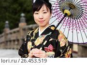 Купить «Японская девушка в кимоно и с зонтом на фоне старинного моста», фото № 26453519, снято 30 января 2011 г. (c) Александр Гаценко / Фотобанк Лори