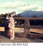 Купить «Японская девушка в светлом кимоно и с зонтом стоит на старинном мосту на фоне вулкана», фото № 26453523, снято 30 января 2011 г. (c) Александр Гаценко / Фотобанк Лори