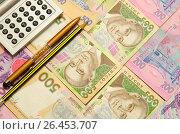 Купить «Ручка,карандаш и калькулятор лежат на купюрах украинских денег», фото № 26453707, снято 14 мая 2017 г. (c) Игорь Кутателадзе / Фотобанк Лори