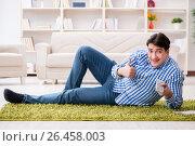 Купить «Young handsome man sitting on floor at home», фото № 26458003, снято 15 марта 2017 г. (c) Elnur / Фотобанк Лори