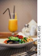 Купить «Seafood salad on the table in the cafe. Orange freshly squeezed juice on the background. indoor. Knife and fork near the plate», фото № 26470495, снято 5 июня 2017 г. (c) Ксения Левашова / Фотобанк Лори
