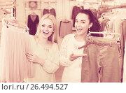 Купить «Female customers selecting skirt and trousers», фото № 26494527, снято 17 августа 2018 г. (c) Яков Филимонов / Фотобанк Лори
