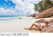 Купить «Woman reading book on picture perfect beach Anse Patates on La Digue Island, Seychelles», фото № 26505615, снято 21 августа 2019 г. (c) Matej Kastelic / Фотобанк Лори