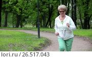 Купить «Пожилая женщина бежит по парковой дорожке, занятие спортом», видеоролик № 26517043, снято 11 июня 2017 г. (c) Кекяляйнен Андрей / Фотобанк Лори