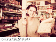 Купить «Young female client is searching for reliable compact powder», фото № 26518847, снято 21 февраля 2017 г. (c) Яков Филимонов / Фотобанк Лори