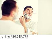 Купить «man shaving beard with razor blade at bathroom», фото № 26519779, снято 15 января 2016 г. (c) Syda Productions / Фотобанк Лори