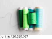 Купить «green and blue thread spools on table», фото № 26520067, снято 29 сентября 2016 г. (c) Syda Productions / Фотобанк Лори