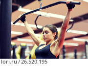 Купить «woman flexing arm muscles on cable machine in gym», фото № 26520195, снято 12 декабря 2015 г. (c) Syda Productions / Фотобанк Лори