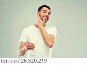 Купить «happy young man applying cream or lotion to face», фото № 26520219, снято 15 января 2016 г. (c) Syda Productions / Фотобанк Лори