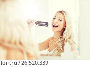 Купить «happy woman singing to hair brush at bathroom», фото № 26520339, снято 13 февраля 2016 г. (c) Syda Productions / Фотобанк Лори