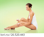Купить «woman applying moisturizing cream to her leg», фото № 26520443, снято 9 апреля 2017 г. (c) Syda Productions / Фотобанк Лори