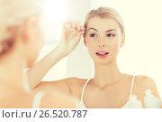 Купить «woman with tweezers tweezing eyebrow at bathroom», фото № 26520787, снято 13 февраля 2016 г. (c) Syda Productions / Фотобанк Лори