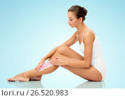 Купить «woman removing leg hair with depilatory wax strip», фото № 26520983, снято 9 апреля 2017 г. (c) Syda Productions / Фотобанк Лори