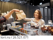 Купить «woman taking paper bag from seller at cafe», фото № 26521071, снято 17 ноября 2016 г. (c) Syda Productions / Фотобанк Лори
