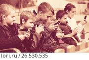 Купить «Outdoor portrait of girls and boys playing with phones», фото № 26530535, снято 21 апреля 2019 г. (c) Яков Филимонов / Фотобанк Лори