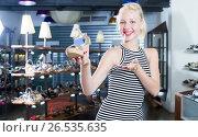 Купить «Happy woman shopaholic holding desired shoe», фото № 26535635, снято 21 марта 2019 г. (c) Яков Филимонов / Фотобанк Лори