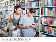 Купить «Smiling teenagers holding book and reading together», фото № 26535767, снято 16 сентября 2016 г. (c) Яков Филимонов / Фотобанк Лори