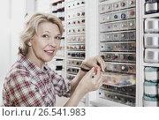 Купить «Mature glad woman customer picking various buttons», фото № 26541983, снято 23 мая 2019 г. (c) Яков Филимонов / Фотобанк Лори