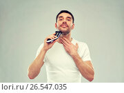 Купить «smiling man shaving beard with trimmer over gray», фото № 26547035, снято 15 января 2016 г. (c) Syda Productions / Фотобанк Лори
