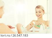 Купить «young woman with lotion washing face at bathroom», фото № 26547183, снято 13 февраля 2016 г. (c) Syda Productions / Фотобанк Лори