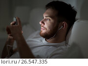 Купить «man with smartphone and earphones in bed at night», фото № 26547335, снято 26 ноября 2016 г. (c) Syda Productions / Фотобанк Лори