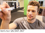 Купить «happy young man with marker writing in gym», фото № 26547367, снято 19 февраля 2017 г. (c) Syda Productions / Фотобанк Лори