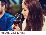 Купить «smiling woman drinking red wine at restaurant», фото № 26547483, снято 8 ноября 2015 г. (c) Syda Productions / Фотобанк Лори