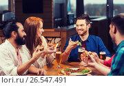 Купить «friends eating pizza with beer at restaurant», фото № 26547491, снято 8 ноября 2015 г. (c) Syda Productions / Фотобанк Лори